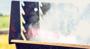 Un vecchio barbecue di cottura a vapore arrugginito quando si accendono nel giardino Immagine Stock Libera da Diritti