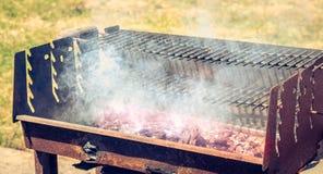 Un vecchio barbecue di cottura a vapore arrugginito quando si accendono nel giardino Fotografia Stock