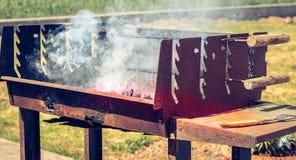 Un vecchio barbecue di cottura a vapore arrugginito quando si accendono nel giardino Fotografie Stock