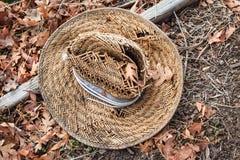 Un vecchio cappello di paglia tessuto su un letto delle foglie di autunno marroni fotografia stock