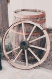 Un vecchio cartwheel di legno fa una pausa un barilotto di legno immagine stock