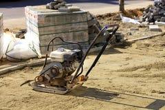 Un vecchio compattatore della benzina per comprimere i supporti sabbiosi del suolo di fronte ad una pila di lastre per pavimentaz immagine stock libera da diritti