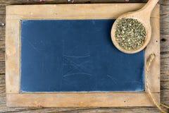 Un vecchio cucchiaio di legno con le bugie tagliuzzate del basilico su una vecchia lavagna dell'ardesia immagini stock libere da diritti