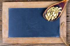 Un vecchio cucchiaio di legno con le intere bugie dei baccelli del cardamomo su un vecchio bordo dell'ardesia fotografia stock