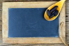 Un vecchio cucchiaio di legno con le intere bugie dei fagioli di tonka su una vecchia lavagna dell'ardesia fotografia stock libera da diritti