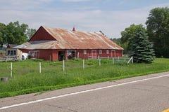 Un vecchio granaio rosso con un tetto arrugginito del metallo Fotografia Stock Libera da Diritti