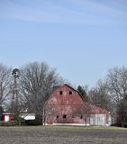 Un vecchio granaio rosso e un segnavento Fotografia Stock