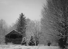 Un vecchio granaio rustico dopo una bufera di neve fotografia stock