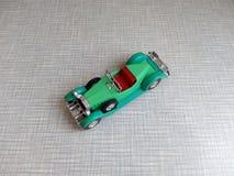 un vecchio modello verde dell'automobile su un fondo grigio Fotografia Stock