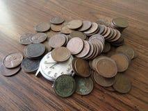 Un vecchio orologio in un mucchio di vecchi penies del grano, Il tempo è denaro Fotografia Stock