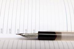 Un vecchio penna-supporto con una penna si trova su un taccuino aperto Primo piano Fuoco selettivo Fotografia Stock Libera da Diritti