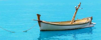 Un vecchio peschereccio di legno sul backgrounde blu Immagini Stock