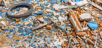 Un vecchio pneumatico in una zona di vetro rotta Immagine Stock
