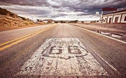 Un vecchio schermo dell'itinerario 66 verniciato sulla strada Fotografie Stock Libere da Diritti