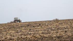 Un vecchio trattore ara un campo con un aratro Immagini Stock