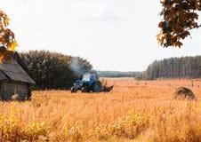 Un vecchio trattore ara un campo in un villaggio nei precedenti una foresta, una vecchia capanna rovinata, un giorno di estate, a immagine stock