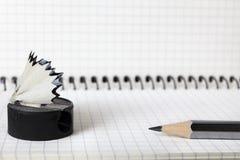 Un vecchio, un di seconda mano, affilatrice con trucioli e una matita semplice si trovano sul taccuino in una scatola Fuoco selet Immagine Stock