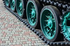 Un veicolo militare sui cingoli sta su un quadrato delle pietre per lastricati La foto dei trattori a cingoli verdi con metallo s Immagine Stock Libera da Diritti