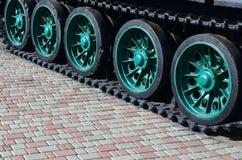 Un veicolo militare sui cingoli sta su un quadrato delle pietre per lastricati La foto dei trattori a cingoli verdi con metallo s Fotografia Stock