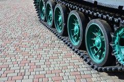 Un veicolo militare sui cingoli sta su un quadrato delle pietre per lastricati La foto dei trattori a cingoli verdi con metallo s Immagini Stock Libere da Diritti