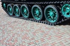 Un veicolo militare sui cingoli sta su un quadrato delle pietre per lastricati La foto dei trattori a cingoli verdi con metallo s Immagini Stock