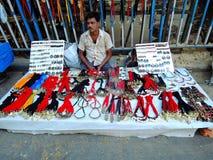 Un vendedor ambulante que vende artículos ornamentales Imagen de archivo libre de regalías