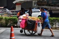 Un vendedor busca al cliente en una calle del centro de ciudad en Bangkok Foto de archivo