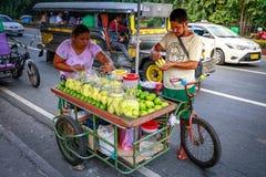 Un vendedor de comida de la calle corta el mango verde fresco que vende en foo foto de archivo