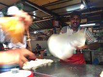 Un vendedor de comida local de la calle que hace el pan del pratha también conocido como pan del vuelo Fotografía de archivo libre de regalías