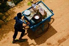 Un vendedor joven de la comida de la calle que camina en el camino en Bangalore imagenes de archivo