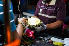 Un vendedor que muestra la fruta del durian al Durian turístico - una fruta exótica con un olor muy desagradable y agudo se vende fotografía de archivo