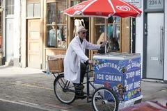 Un vendeur plus âgé de crème glacée dans une robe longue blanche monte une bicyclette avec son chariot de crème glacée  Image libre de droits
