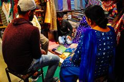 Un venditore vende la seta a Varanasi, India Fotografia Stock Libera da Diritti