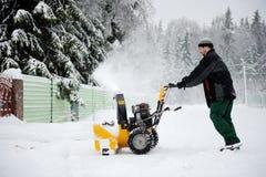 Un ventilador de nieve del funcionamiento del hombre Imagen de archivo libre de regalías