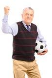 Un ventilador maduro feliz con fútbol que gesticula con su mano Imagen de archivo