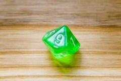 Un verde translúcido diez echó a un lado jugando dados en un backgroun de madera Fotos de archivo