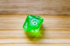 Un verde translúcido diez echó a un lado jugando dados en un backgroun de madera Fotografía de archivo