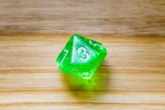 Un verde translúcido diez echó a un lado jugando dados en un backgroun de madera Fotografía de archivo libre de regalías
