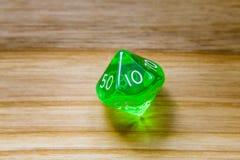 Un verde translúcido diez echó a un lado jugando dados en un backgroun de madera Imagenes de archivo