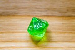 Un verde translúcido diez echó a un lado jugando dados en un backgroun de madera Imagen de archivo