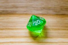 Un verde translúcido diez echó a un lado jugando dados en un backgroun de madera Imágenes de archivo libres de regalías
