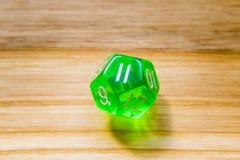 Un verde translúcido doce echó a un lado jugando dados en un backgr de madera Imágenes de archivo libres de regalías