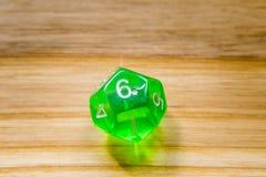 Un verde translúcido doce echó a un lado jugando dados en un backgr de madera Foto de archivo
