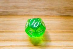 Un verde translúcido doce echó a un lado jugando dados en un backgr de madera Foto de archivo libre de regalías