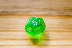 Un verde translúcido doce echó a un lado jugando dados en un backgr de madera Fotos de archivo