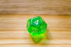 Un verde translúcido doce echó a un lado jugando dados en un backgr de madera Fotografía de archivo