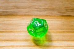 Un verde translúcido doce echó a un lado jugando dados en un backgr de madera Imagenes de archivo