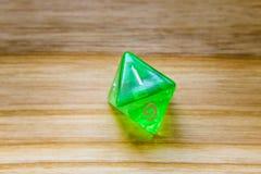 Un verde translúcido ocho echó a un lado jugando dados en un backgro de madera Imagen de archivo