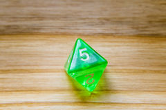 Un verde translúcido ocho echó a un lado jugando dados en un backgro de madera Fotografía de archivo libre de regalías