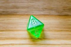 Un verde translúcido ocho echó a un lado jugando dados en un backgro de madera Fotos de archivo